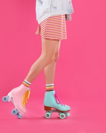 Young woman with retro roller skates on color background, closeup